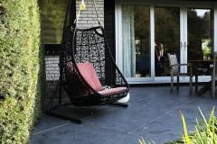 terras-aangelegd-met-keramische-tegels-antaciet-gekleurd-siergras-schommelstoel